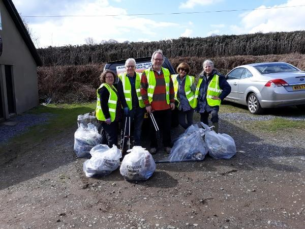 five people in high vis jackets with bags of litter